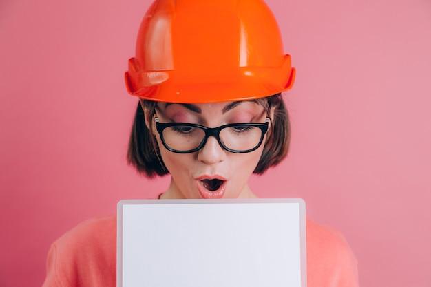 꽤 놀된 놀된 여자 작업자 작성기 분홍색 배경에 흰색 사인 보드를 빈 개최. 건물 헬멧.