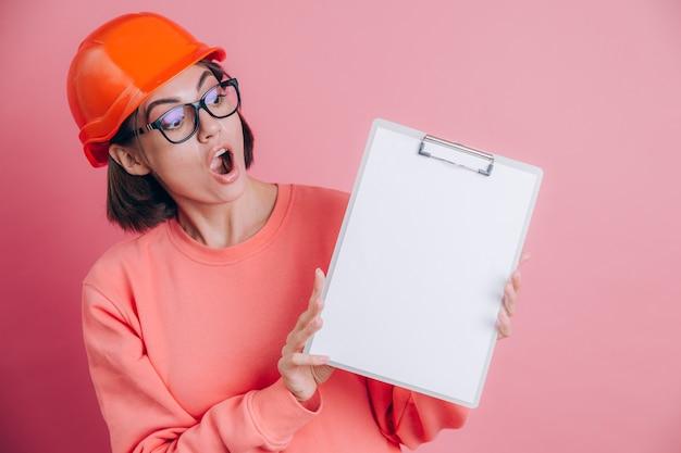Il costruttore sorpreso abbastanza stupito del lavoratore della donna tiene il bordo bianco del segno in bianco contro fondo rosa. casco da costruzione.