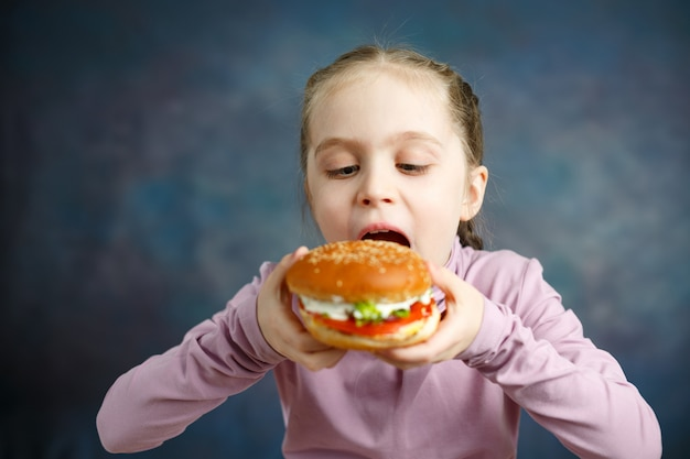 Pretty american little girl eating burger. unhealthy eating concepts.