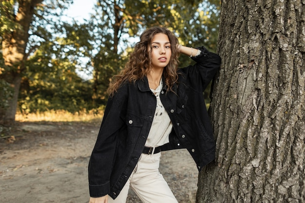 스웨터가 달린 데님 블랙 재킷에 곱슬머리를 한 예쁜 미국 모델 소녀가 서서 자연의 나무 근처에서 카메라를 봅니다. 여름 캐주얼 여성스러운 스타일과 아름다움