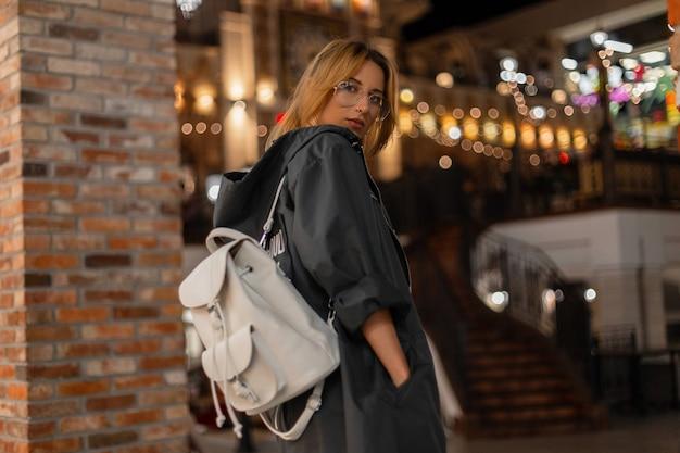 세련 된 흰색 배낭 세련 된 안경에 후드와 함께 세련 된 재킷에 예쁜 미국 젊은 여자는 쇼핑 센터에 산책. 예쁜 여자 패션 모델은 주말을 즐깁니다. 괴로움