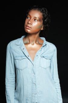 블랙 위에 서있는 빛나는 메이크업으로 예쁜 미국 젊은 여자