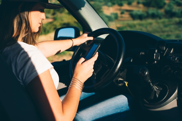 Красивая и привлекательная белокурая девушка с кепкой управляет телефоном в оранжевом фургоне