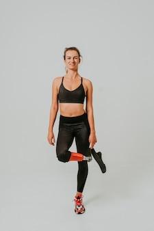다리 장애가있는 예쁘고 자신감있는 여성이 운동을하고 있습니다.