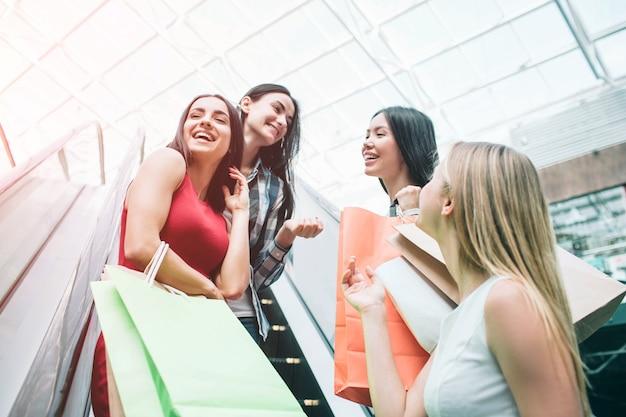 예쁘고 행복한 소녀는 에스컬레이터에 서서 웃고 있습니다.