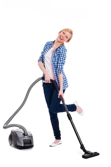 예쁘고 웃는 여자는 바닥을 진공 청소기로 청소