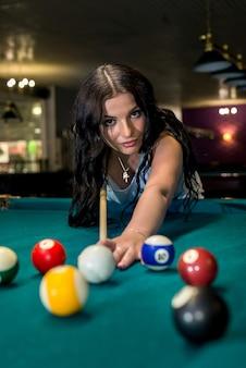 술집에서 당구를 재생하는 예쁘고 젊은 여자