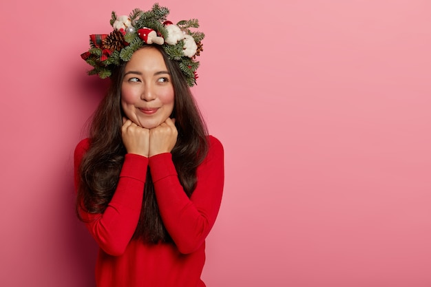 彼女の頭にクリスマスリースを着ているきれいで若い女性