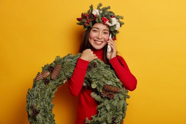 그녀의 머리에 크리스마스 화 환을 입고 예쁘고 젊은 여자