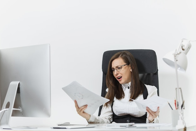Pretty angry business woman in suit sitting at the desk with documents, working at computer with modern monitor in light office, swearing and screaming, resolving issues,