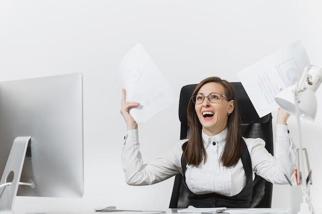 Donna d'affari piuttosto arrabbiata in tuta seduta alla scrivania con documenti, lavorando al computer con monitor moderno in ufficio leggero, imprecando e urlando, risolvendo problemi,