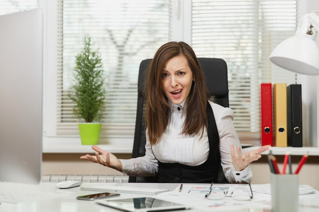 Pretty angry business woman in suit sitting at the desk with tablet, working at computer with modern monitor with documents in light office, swearing and screaming, resolving issues, emotion concept.