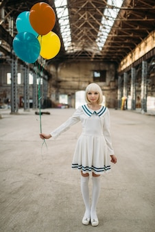 Pretty anime style blonde girl poses with colorful air balloons. cosplay fashion, asian culture, doll in dress, cute woman with makeup in the factory shop