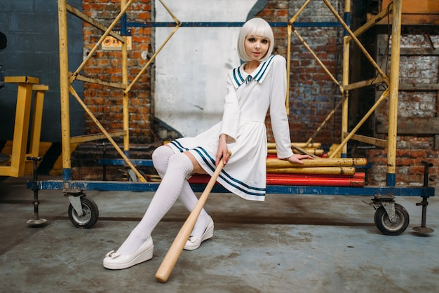 Pretty anime style blonde girl with baseball bat. cosplay fashion, asian culture, doll in uniform, cute woman with makeup in the factory shop