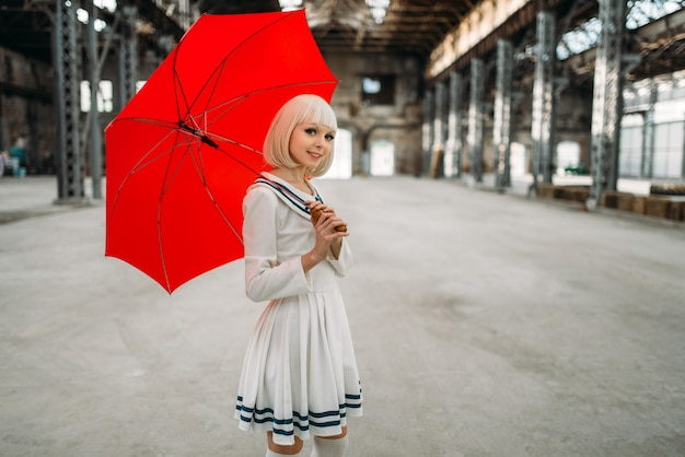 Pretty anime style blonde girl with red umbrella. cosplay fashion, asian culture, doll in dress, cute woman with makeup in the factory shop