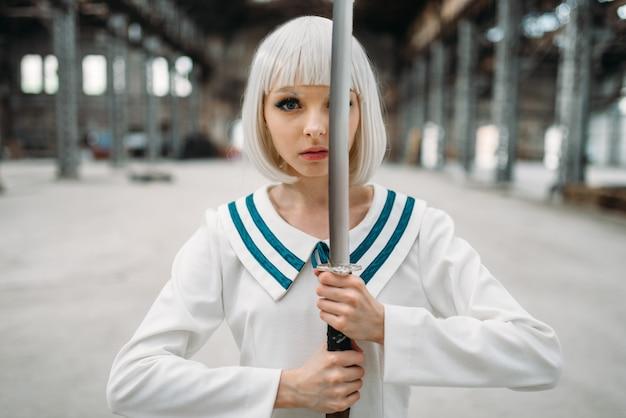 Блондинка девушка довольно аниме стиль с мечом. мода для косплея, азиатская культура, кукла с лезвием на заброшенной фабрике, милая женщина с макияжем