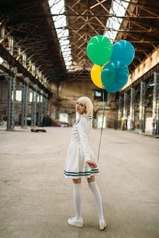 Pretty anime style blonde lady with colorful air balloons. cosplay fashion, asian culture, doll in dress, cute woman with makeup in the factory shop