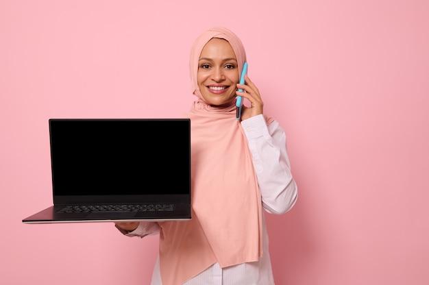 분홍색 히잡을 쓴 예쁜 아랍 이슬람 여성은 휴대전화로 말을 하고 이빨 미소를 지으며 카메라에 복사 공간이 있는 빈 검은색 모니터 화면을 보여줍니다. 격리 된 컬러 파스텔 배경