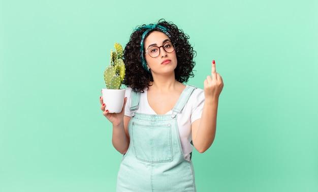 怒って、イライラして、反抗的で攻撃的で、鉢植えのサボテンを持っているかなりアラブの女性