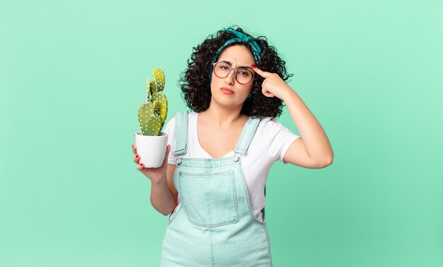 かなりアラブの女性が混乱して困惑していると感じ、あなたが正気でないことを示し、鉢植えのサボテンを持っている