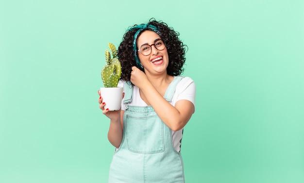 幸せを感じ、挑戦に直面している、または鉢植えのサボテンを祝って保持しているかなりアラブの女性