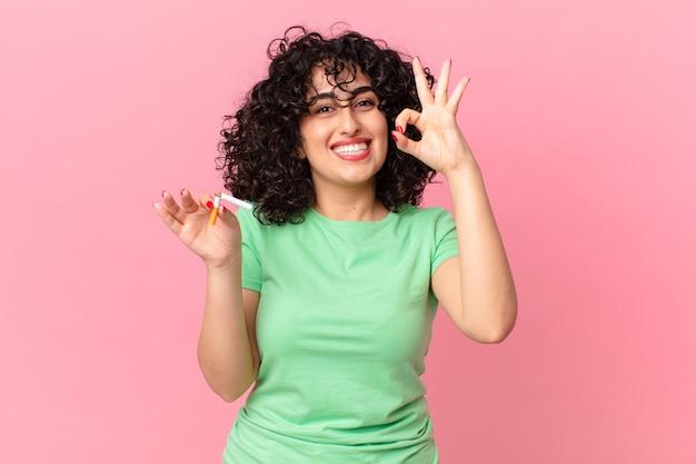 예쁜 아랍 여성이 행복해하며 괜찮은 제스처로 승인을 보여줍니다. 금연 개념