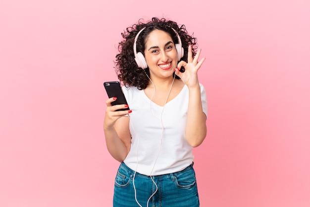 Довольно арабская женщина чувствует себя счастливой, демонстрируя одобрение жестом в наушниках и смартфоне