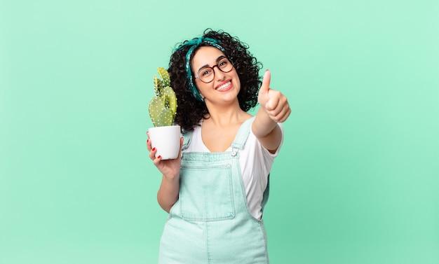 かなりアラブの女性が誇りを感じ、親指を立てて前向きに笑い、鉢植えのサボテンを持っています