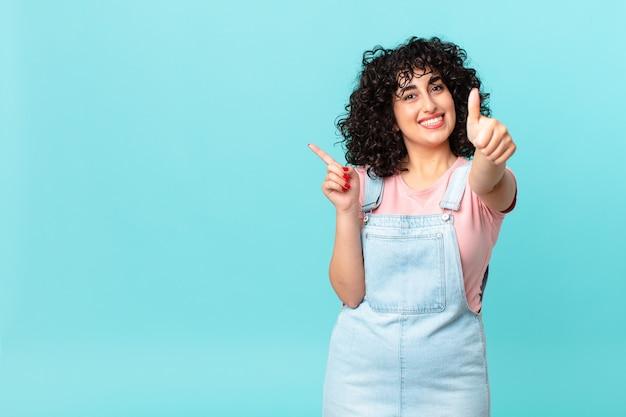 かなりアラブの女性が誇りを感じ、親指を立てて前向きに笑っている