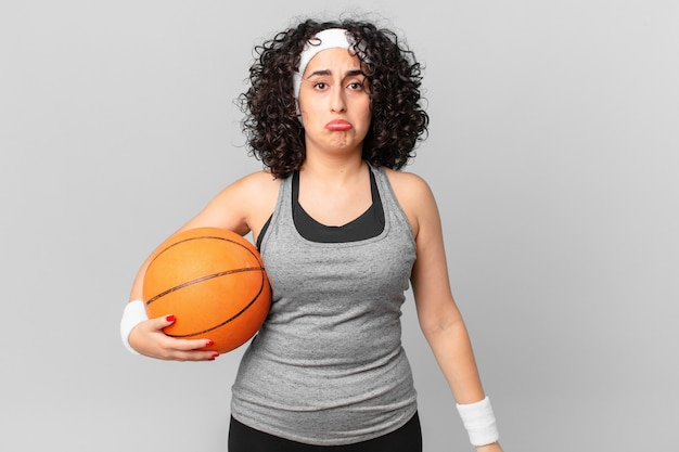 Pretty arab woman feeling sad and whiney with an unhappy look and crying and holding a basketball ball. sport concept