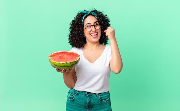 예쁜 아랍 여성은 충격을 받고 웃고 성공을 축하하며 수박을 들고 있습니다. 여름 개념