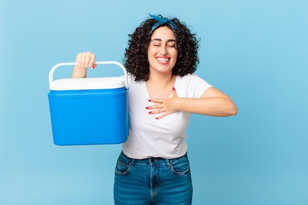 재미있는 농담에 큰 소리로 웃고 휴대용 냉장고를 들고 있는 예쁜 아랍 여성
