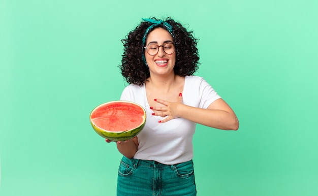 웃긴 농담에 큰 소리로 웃으면서 수박을 들고 있는 예쁜 아랍 여성. 여름 개념