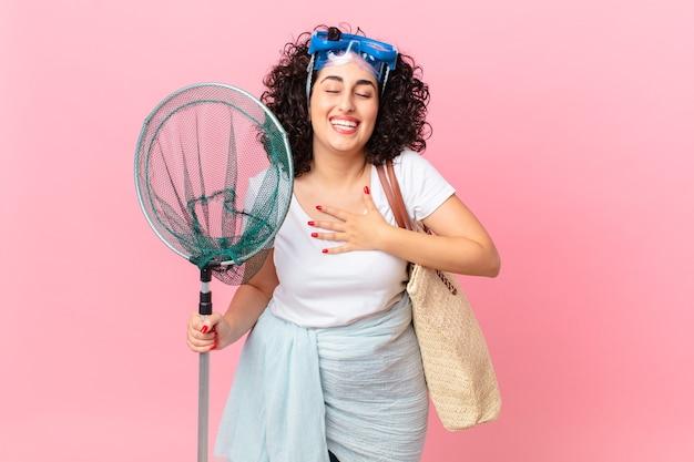고글을 들고 우스꽝스러운 농담을 하며 큰 소리로 웃고 있는 예쁜 아랍 여성. 피셔 개념