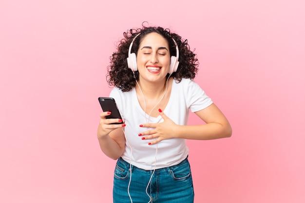 헤드폰과 스마트폰으로 재미있는 농담에 큰 소리로 웃고 있는 예쁜 아랍 여성