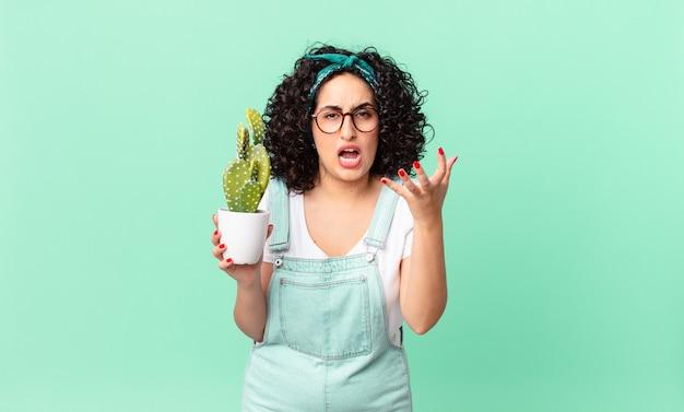 怒って、イライラして欲求不満に見え、鉢植えのサボテンを持っているかなりアラブの女性