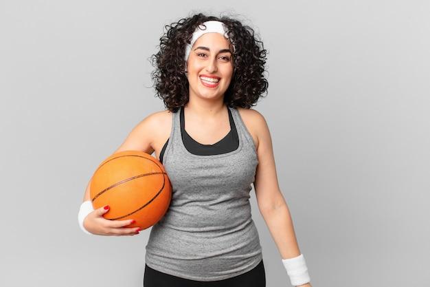 幸せそうに見えて、嬉しそうに驚いて、バスケットボールのボールを持っているかなりアラブの女性。スポーツコンセプト