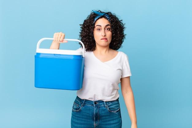 어리둥절하고 혼란스러워 보이는 예쁜 아랍 여성이 휴대용 냉장고를 들고 있다