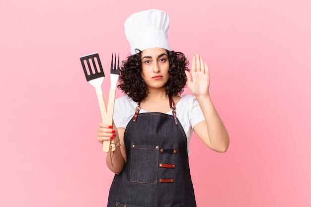 Довольно арабская женщина выглядит серьезной, показывая открытую ладонь, делая стоп-жест. концепция шеф-повара барбекю