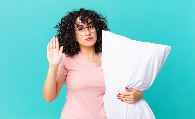 Pretty arab woman looking serious showing open palm making stop gesture. wearing pajamas and holding a pillow