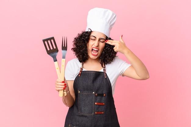불행하고 스트레스를 받고 있는 예쁜 아랍 여성, 자살 제스처가 총기 표시를 하고 있습니다. 바베큐 요리사 개념