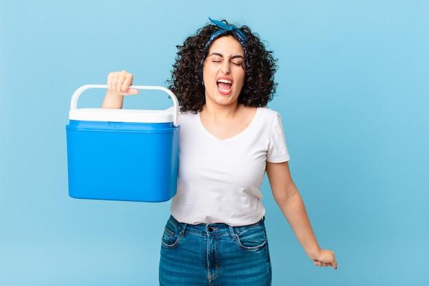 매우 화난 표정을 지으며 휴대용 냉장고를 들고 공격적으로 외치는 예쁜 아랍 여성