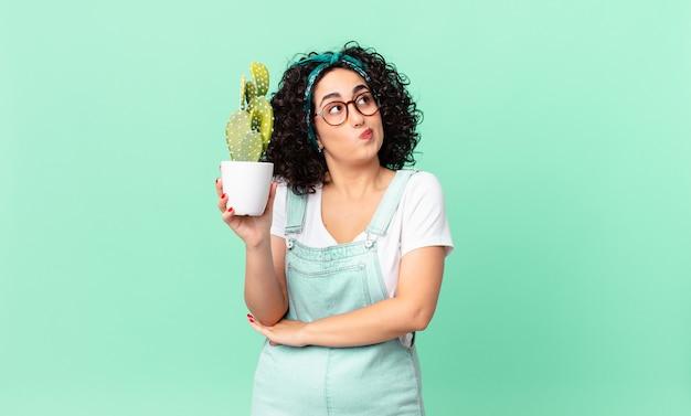 肩をすくめる、混乱して不確かな感じ、鉢植えのサボテンを持っているかなりアラブの女性