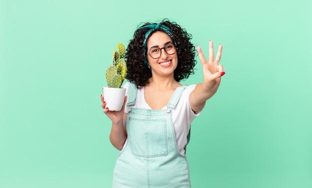 笑顔でフレンドリーに見えるかなりアラブの女性、3番目を示し、鉢植えのサボテンを持っています