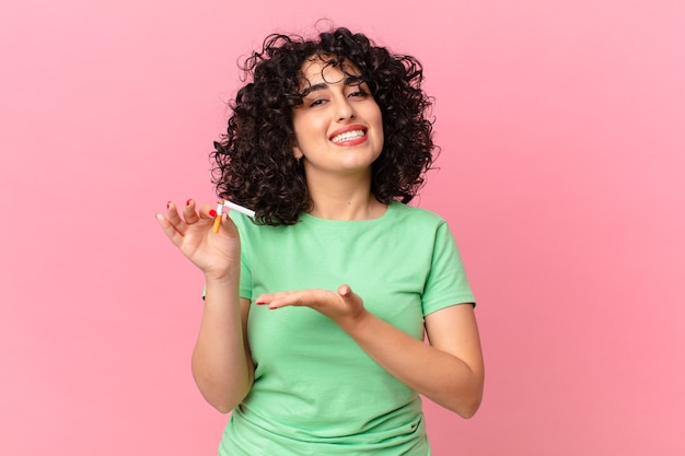 예쁜 아랍 여성이 즐겁게 웃고 행복하고 개념을 보여줍니다. 금연 개념