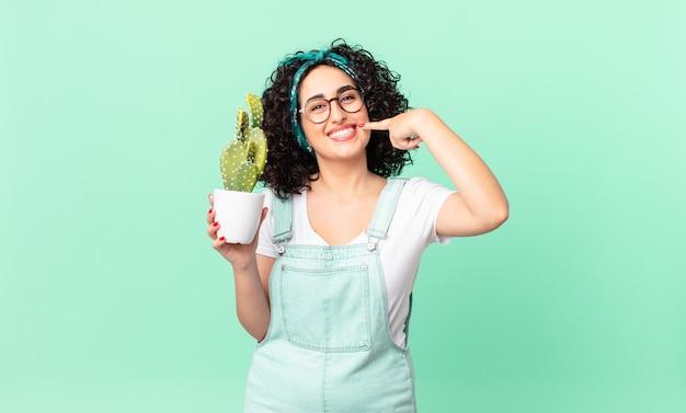 自信を持って笑顔で自分の広い笑顔を指して、鉢植えのサボテンを持っているかなりアラブの女性
