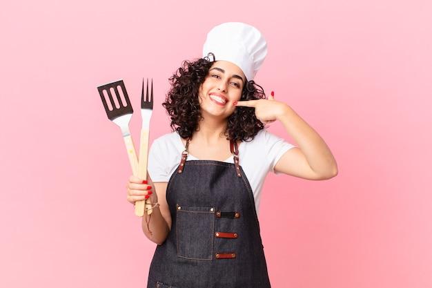 자신의 넓은 미소를 자신있게 가리키며 웃고 있는 예쁜 아랍 여성. 바베큐 요리사 개념
