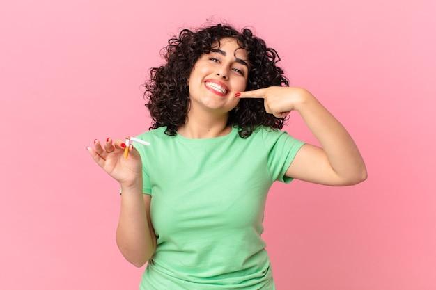 자신의 넓은 미소를 자신있게 가리키며 웃고 있는 예쁜 아랍 여성. 금연 개념