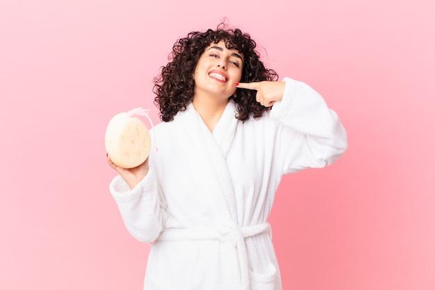 목욕 가운을 입고 스폰지를 들고 자신의 넓은 미소를 자신있게 가리키며 웃고 있는 예쁜 아랍 여성