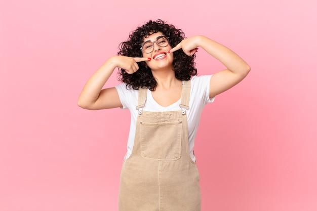 Довольно арабская женщина уверенно улыбается, указывая на собственную широкую улыбку